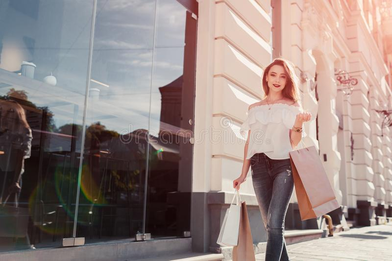 Beautiful stylish young woman with shopping bags walking on city street in summer. Happy girl holding purchases stock photo