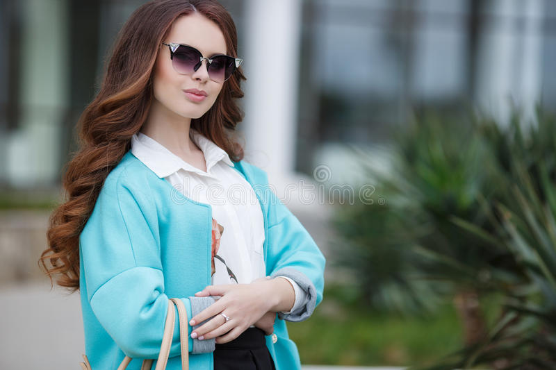 Beautiful stylish young woman on street. Young beautiful brunette woman with long curly hair,wears dark sun glasses,on fingers wearing a ring,dressed in a blue stock photography