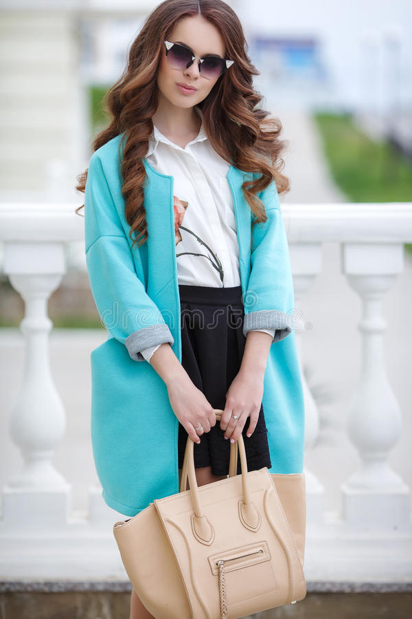 Beautiful stylish young woman on street. Young beautiful brunette woman with long curly hair,wears dark sun glasses,on fingers wearing a ring,dressed in a blue stock images