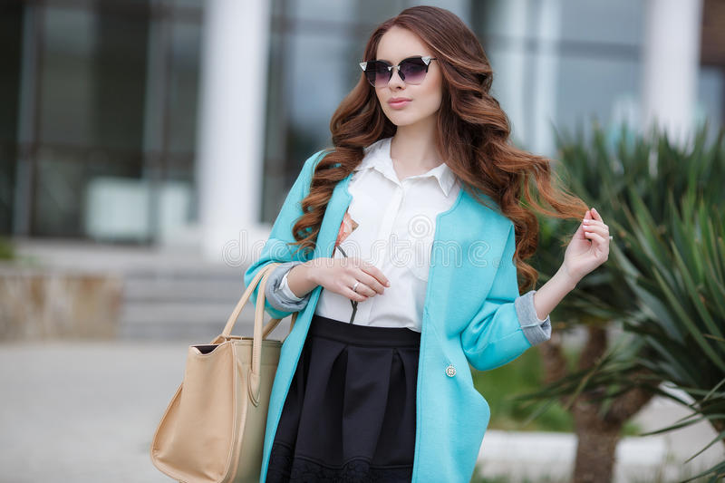 Beautiful stylish young woman on street. Young beautiful brunette woman with long curly hair,wears dark sun glasses,on fingers wearing a ring,dressed in a blue stock image