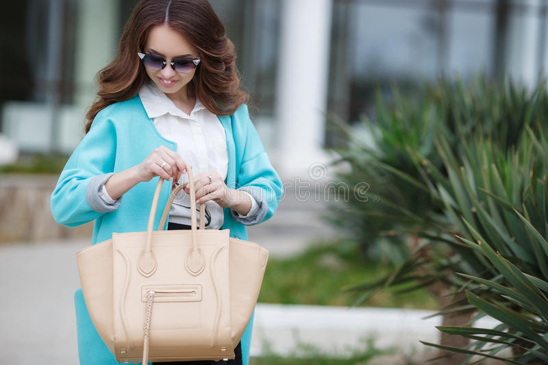 Beautiful stylish young woman on street. Young beautiful brunette woman with long curly hair,wears dark sun glasses,on fingers wearing a ring,dressed in a blue royalty free stock photography