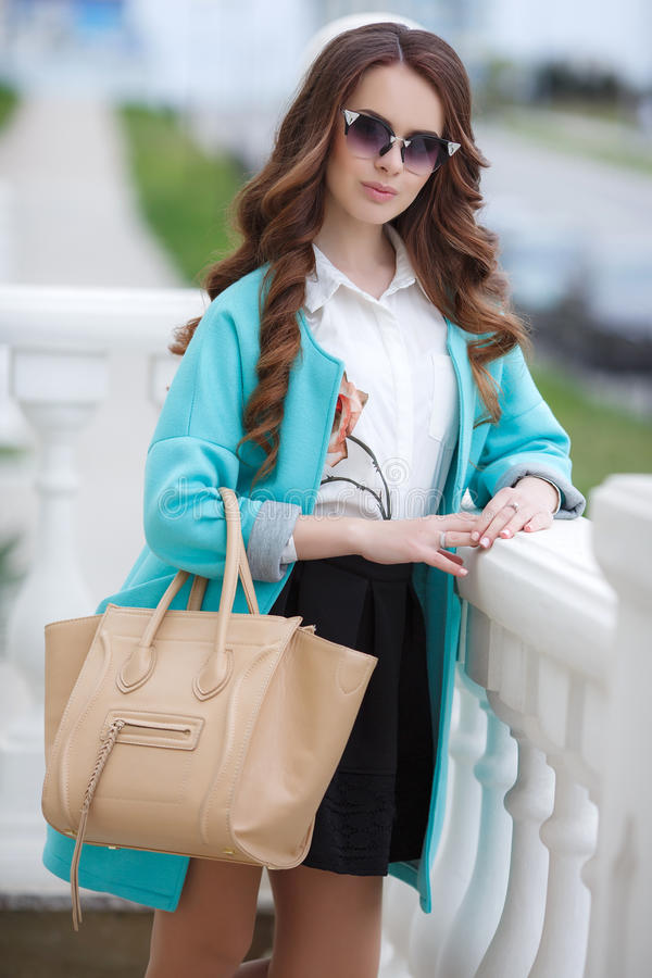 Beautiful stylish young woman on street. Young beautiful brunette woman with long curly hair,wears dark sun glasses,on fingers wearing a ring,dressed in a blue royalty free stock photo
