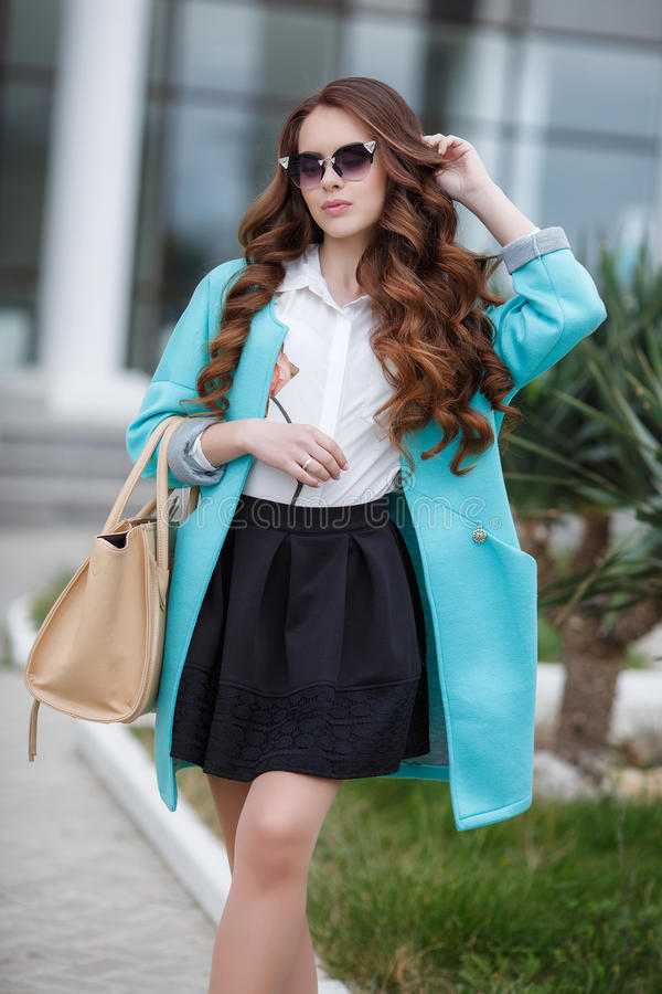 Beautiful stylish young woman on street. Young beautiful brunette woman with long curly hair,wears dark sun glasses,on fingers wearing a ring,dressed in a blue royalty free stock image
