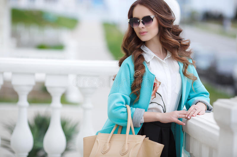 Beautiful stylish young woman on street. Young beautiful brunette woman with long curly hair,wears dark sun glasses,on fingers wearing a ring,dressed in a blue stock photos