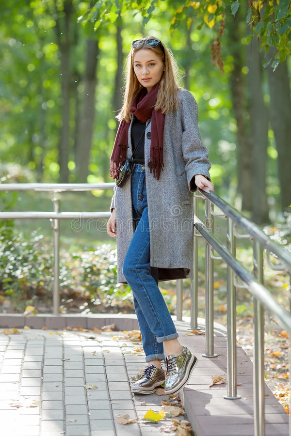 Beautiful stylish young woman in a warm scarf blue jeans trendy shoes and cozy coat walking along in fall city park stock photo
