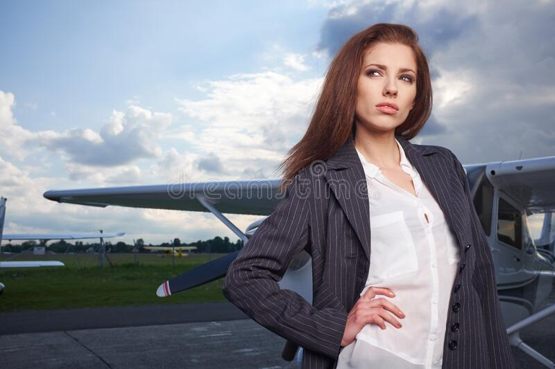 Beautiful successful caucasian young lady wearing stylish  suit in private aircraft. Business, success, travel concept royalty free stock photography
