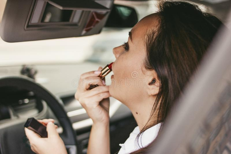 Beautiful successful elegant brunette young woman painting her lips with red lipstick inside car stock photos