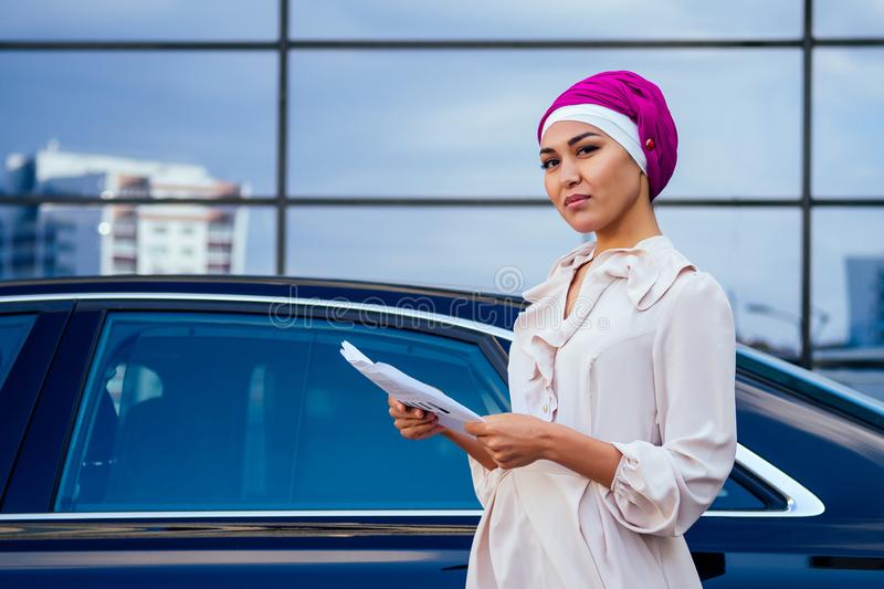 Beautiful and successful mulatto afro muslim business woman entrepreneur in stylish hijab and turban holding paper royalty free stock photo