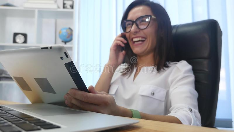 A beautiful successful woman talking on phone at the modern office stock photo