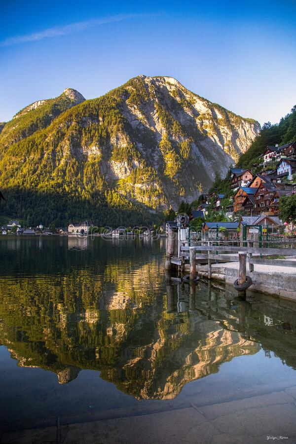 The beautiful summer alpine town of Hallstatt and the mountain lake Hallstatter See at sunrise. Beautiful natural summer stock image