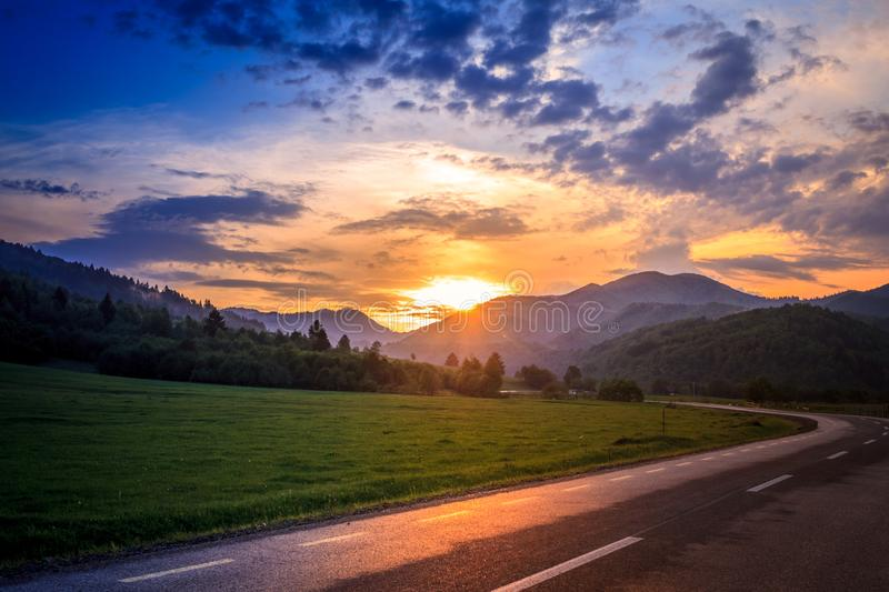 Beautiful summer background with a green nature landscape. scene with hills,trees, colorful sky and sun in summertime. Travel photo shoot taken on the road, in a royalty free stock image