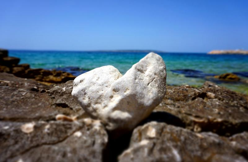 Beautiful summer background with a white heart shaped stone in front of the beautiful blue sea and sky horizon line. White heart shaped stone in front of the royalty free stock images