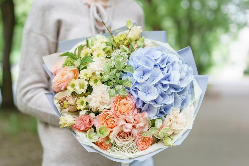 Beautiful summer bouquet. Arrangement with mix flowers. Young girl holding a flower arrangement with hydrangea. The. Concept of a flower shop royalty free stock image