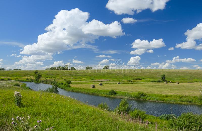 Sunny summer scene with river,fields,green hills,hay bales and beautiful clouds in blue sky. stock images