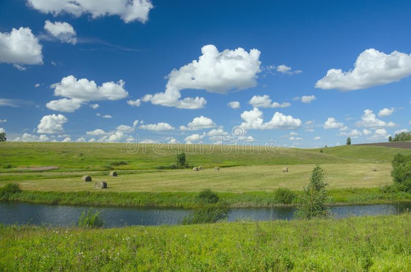 Sunny summer scene with river,fields,green hills,hay bales and beautiful clouds in blue sky. royalty free stock photography
