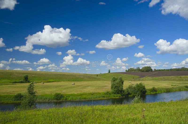 Sunny summer scene with river,fields,green hills,hay bales and beautiful clouds in blue sky. stock photography