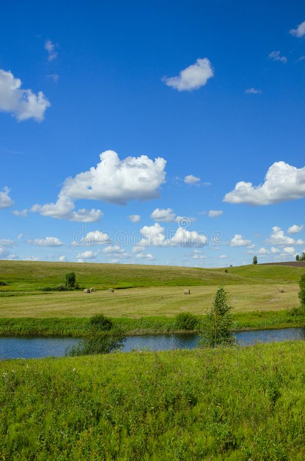 Sunny summer scene with river,fields,green hills,hay bales and beautiful clouds in blue sky. stock photos