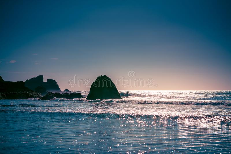 Beautiful summer day at Piha Beach, New Zealand. Beautiful summer afternoon at Piha Beach, New Zealand. Sunlight sparkles all over the waves, rock formations royalty free stock photography