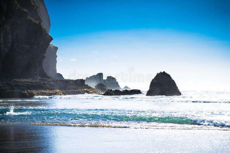 Beautiful summer day at Piha Beach, New Zealand. Sunlight sparkles all over the waves, rock formations partially hidden in th foam stock photography
