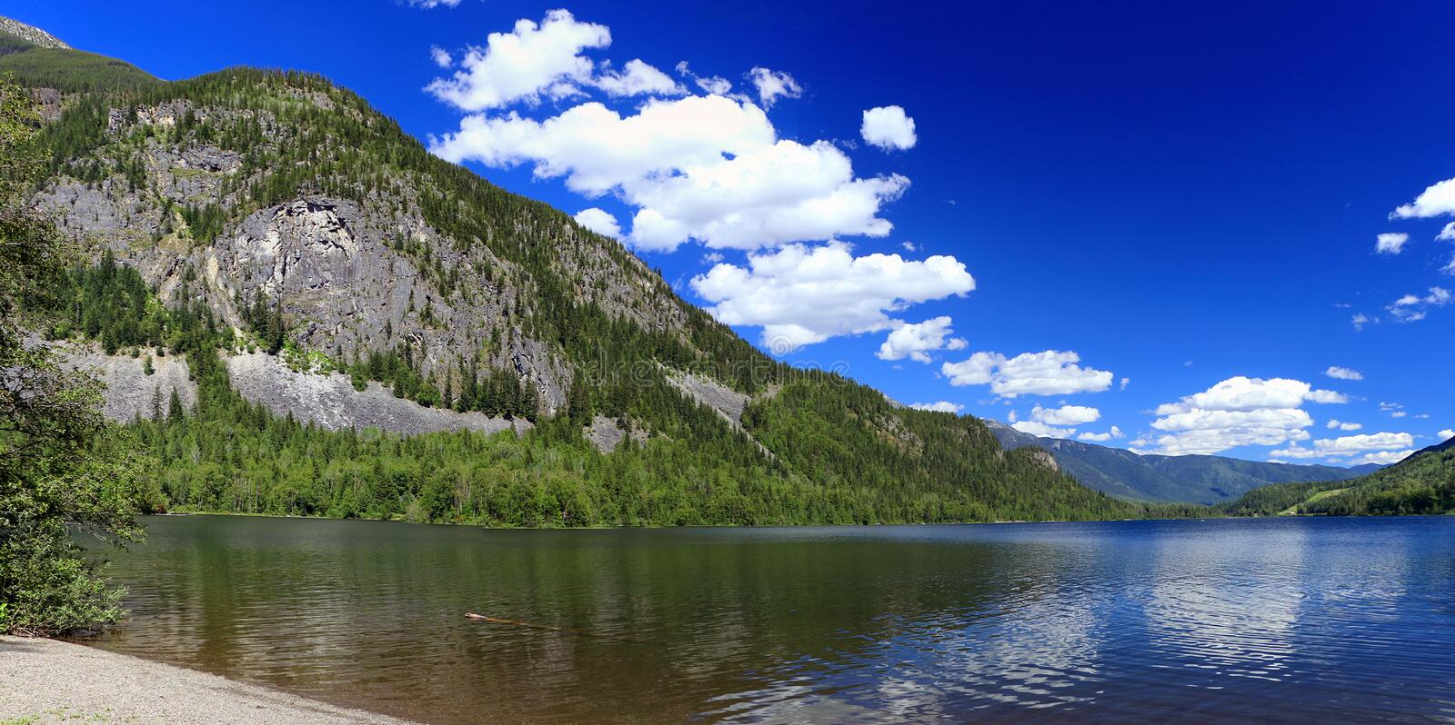 Panorama of Beautiful Summer Day at Summit Lake Provincial Park in the Selkirk Mountains, British Columbia, Canada. Beautiful panorama of clear mountain lake in stock photography