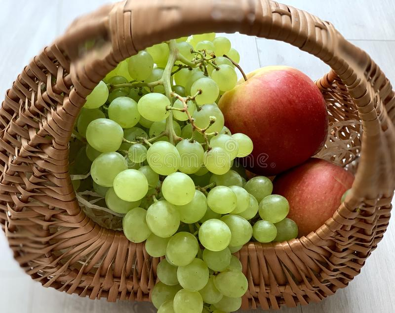 Beautiful summer fruits in a basket. Yellow red apples and white grapes. stock photos