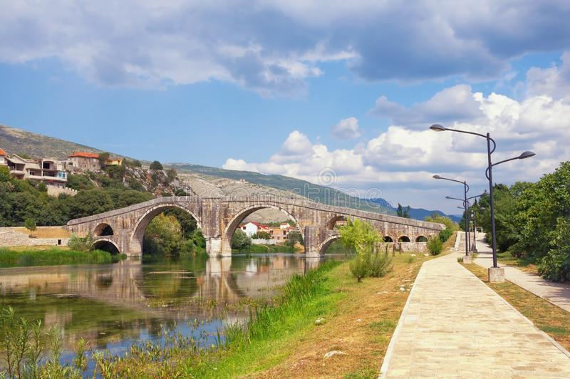 Beautiful summer landscape with old stone bridge. Bosnia and Herzegovina, view of Trebisnjica river, embankment of Trebinje city stock photography