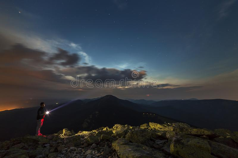 Beautiful summer night in mountains. Profile silhouette of young tourist hiker man with flashlight standing alone on rocky mountai stock image