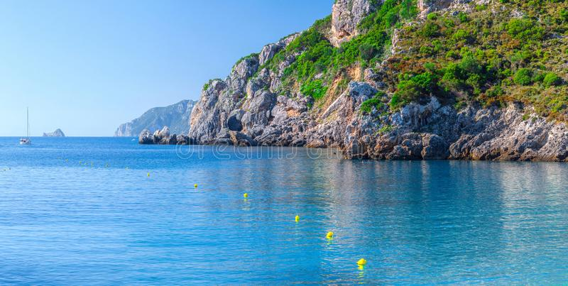 Beautiful summer panoramic seascape. View of the cliff into the sea bay with crystal clear azure water in sunshine daylight. Boats stock photo