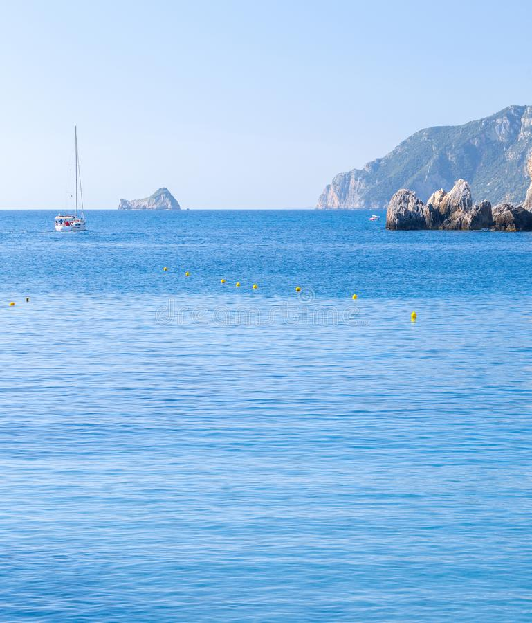 Beautiful summer panoramic seascape. View of the cliff into the sea bay with crystal clear azure water in sunshine daylight. Boats royalty free stock images