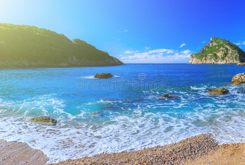Beautiful summer panoramic seascape. View of the coastline into. The sea bays with crystal clear azure water. In the backlight sunbeam light. Paleokastrica stock photography