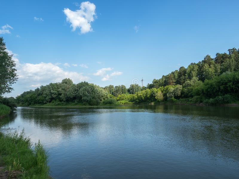 Beautiful summer peige. The blue sky is reflected in a deep river on a bright sunny day. Cloud in the sky stock photos