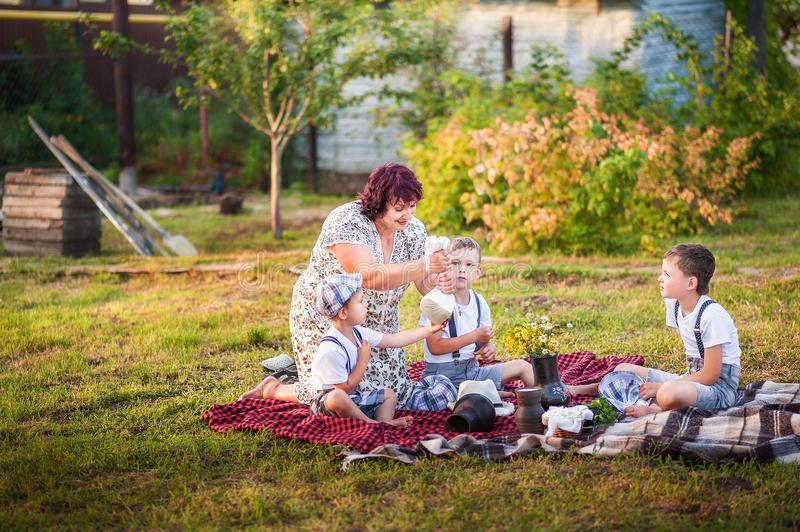 A beautiful summer photo of the family`s pastime. Grandma and grandchildren at sunset make homemade goat cheese. Babes are boys in. Shorts and caps royalty free stock images