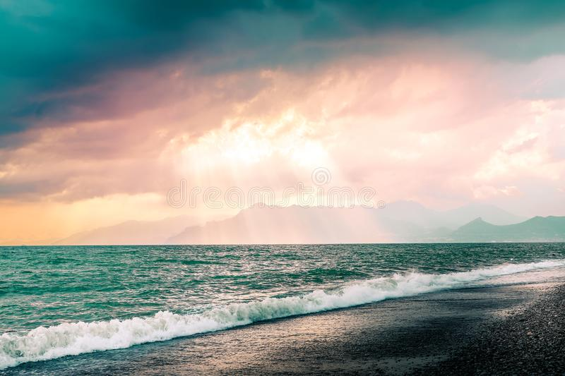 Beautiful summer seascape with mountains silhouette. Cloudy pink sky with sunrays through clouds. Salerno beach, Italy royalty free stock image