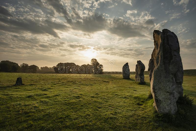 Stunning Summer sunrise landscape of Neolithic standing stones in English cluntryside with gorgeous light with slight background royalty free stock photography