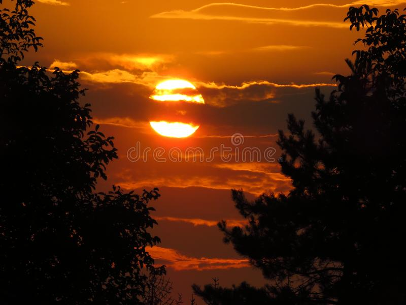 The sun behind clouds. Beautiful summer sunset with amazing colours. Pure photo. No postprocessing no Photoshop correction. royalty free stock photo