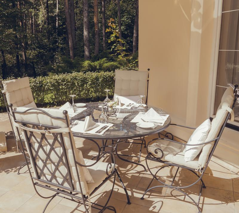 Beautiful summer terrace with garden furniture with white pillows surrounded by greenery on a warm, summer day stock photo