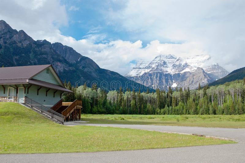 Beautiful summer view of the snow-capped peak of Mount Robson and the log house in the valley stock photo