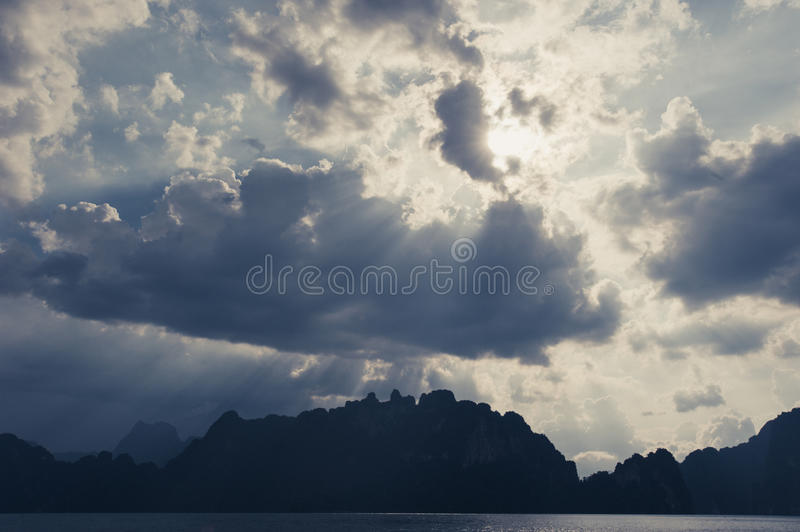 Beautiful sun rays through the clouds over mountains, evening lig. Ht, Amazing scene at Khao-Sok National Park of Thailand royalty free stock photo