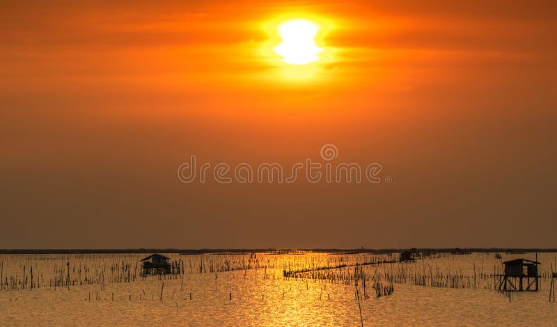 Beautiful sun in summer. Sunset sky over the sea, fisherman`s hut and mangrove forest in the evening. Bamboo pole at coast. Bamboo. Embroidery to slow down the royalty free stock images