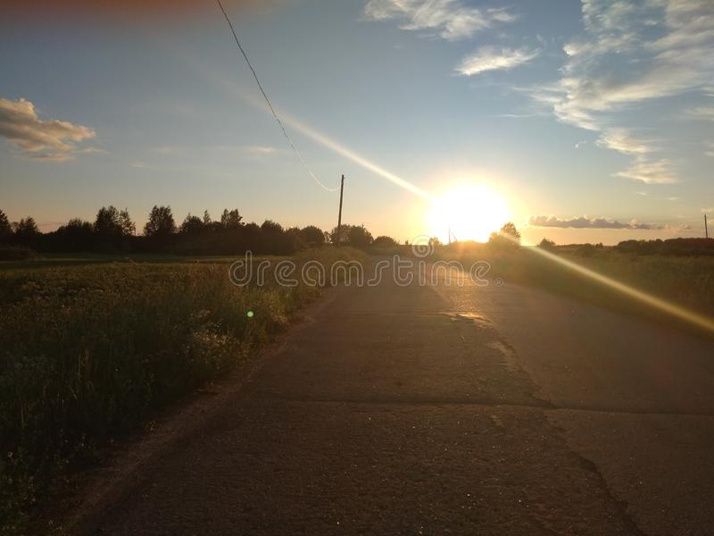 Beautiful sun at sunset and the road. Summer evening, the village, the sun is about to fall over the horizon royalty free stock images