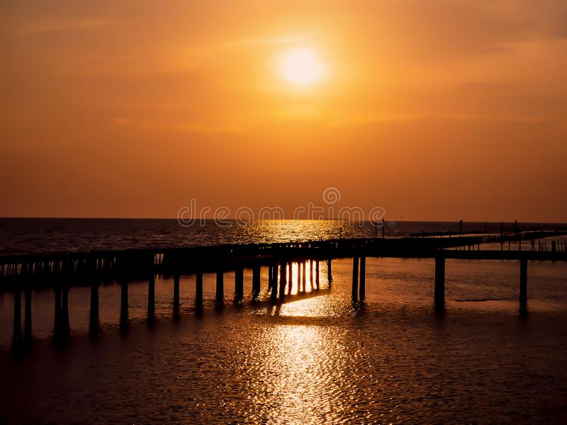 Beautiful sun Wooded bridge pole in the port between sunrise against orange sky calm peaceful moment relax holiday concept idea.  royalty free stock images