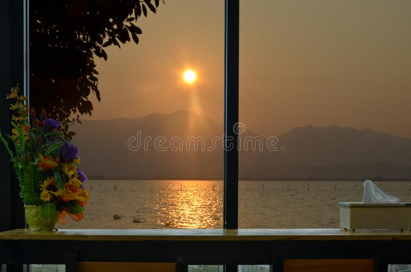 Beautiful sundown over the mountain and the lake in the window view royalty free stock photo
