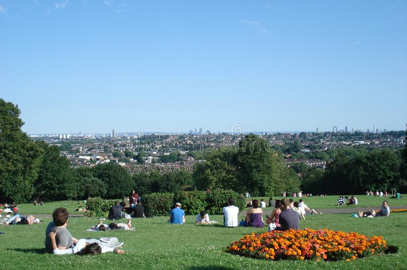 People relaxing on the lawn at park in London stock image