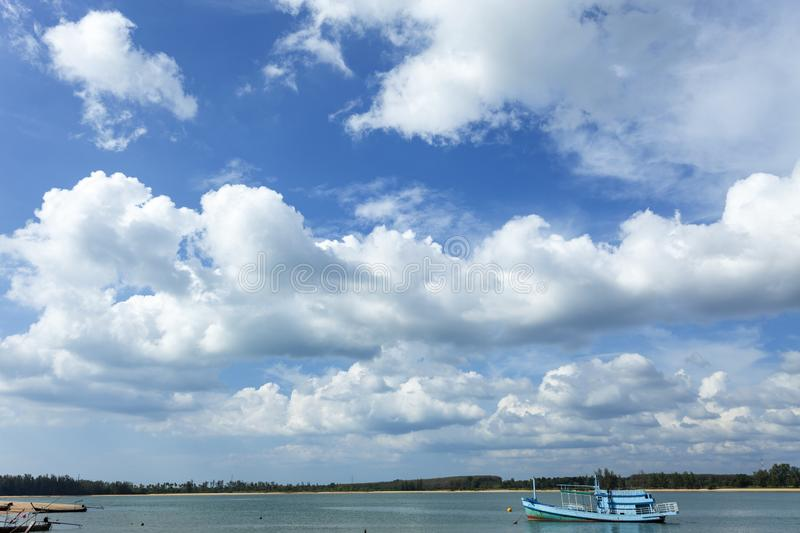 Beautiful sunny day with blue sky white clouds over the sea and fishing boat stock photography