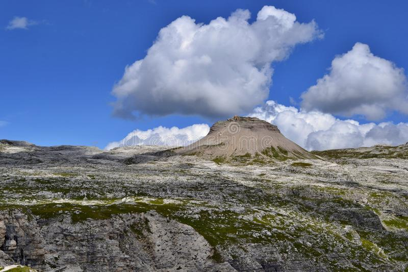 Beautiful sunny day in Dolomites, blue sky, white clouds, high mountains. stock photography