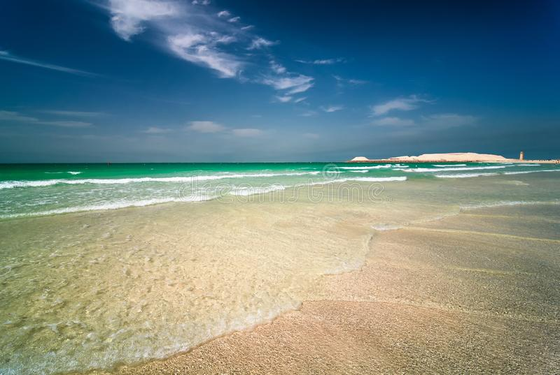 Jumeirah beach in Dubai with crystal clear sea water and amazing blue sky, Dubai, United Arab Emirates. Beautiful sunny Jumeirah beach in Dubai with crystal royalty free stock photography