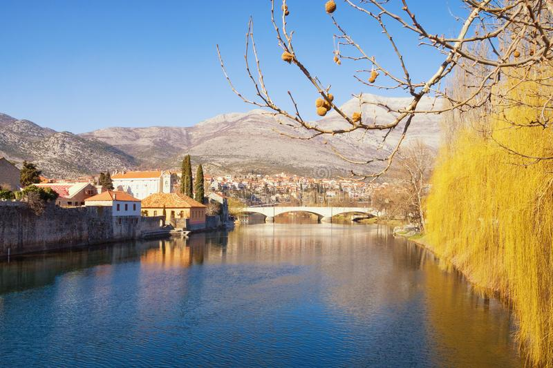 Beautiful sunny landscape, blue sky, yellow trees and ancient city reflected in river water. Bosnia and Herzegovina, Trebinje city. Beautiful sunny landscape royalty free stock photography