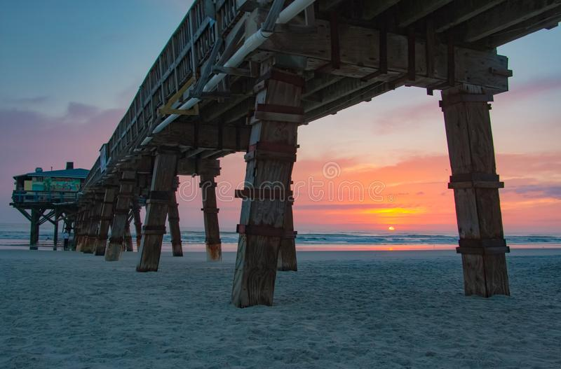 Sunrise at Sunglow Pier in Port Orange Florida. A beautiful sunrise as seen below the Sunglow Pier in Daytona Beach Shores Florida, near Port Orange. The stock image