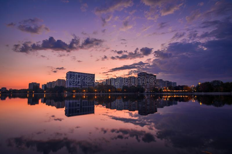 Beautiful sunrise cityscape scene on a lake with mirror reflection royalty free stock images