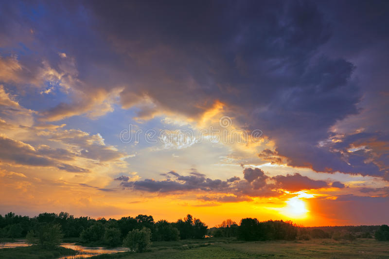 Beautiful sunrise and dramatic clouds on the sky. Flood waters of Narew river, Poland royalty free stock photo